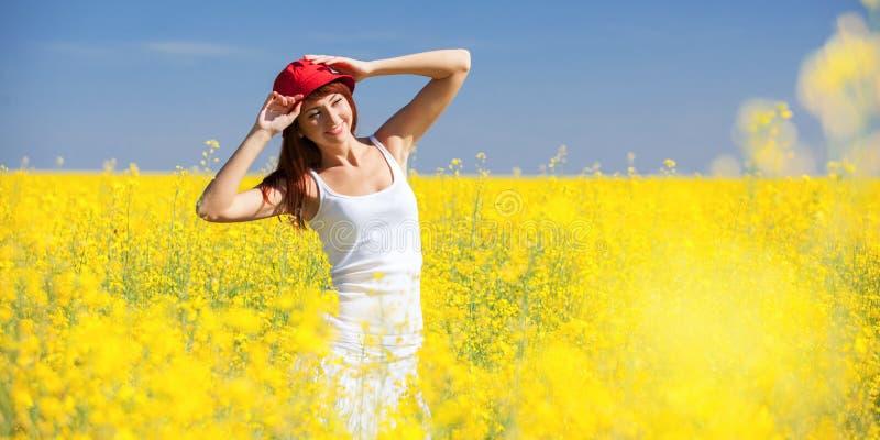 Koncepcja sukcesu w zakresie wolności Szczęśliwa kobieta na polu z kwiatami w słoneczny dzień na wsi Tło piękna natury, zdjęcie stock