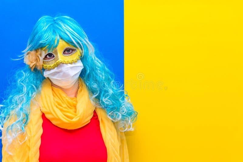 Koncept för skydd mot coronavirus på karnivalsvenice En ljus kvinna i en blå mask och gul karneval mask arkivfoton