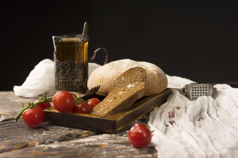 Konceptualny życie pokrojony chleb wciąż, czereśniowi pomidory, szkło zdjęcia stock