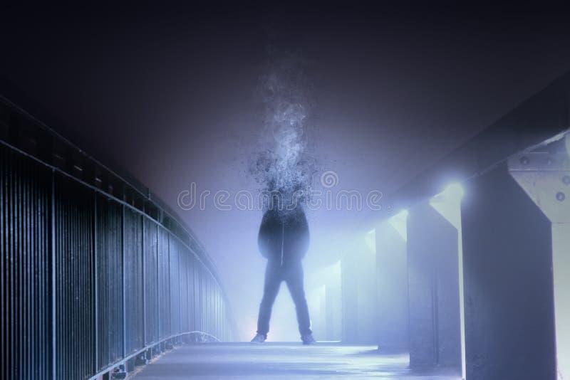 Konceptualny cyfrowy sztuka obrazek mężczyzna który jest głową rozpadał się i obraca w dym, stoi na mgłowej ścieżce przy nocą W obrazy stock