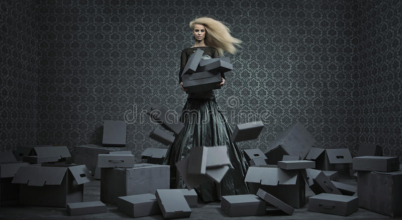 Konceptualny obrazek blond dama wśród mnóstwo pudełek zdjęcia stock