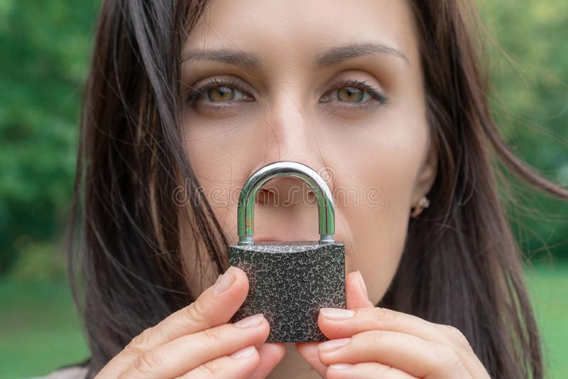 Konceptualny portret kobieta utrzymuje ciszę z kędziorkiem nad jej usta caucasian kobiety utrzymania usta blokujący J?zykowa bari obrazy royalty free