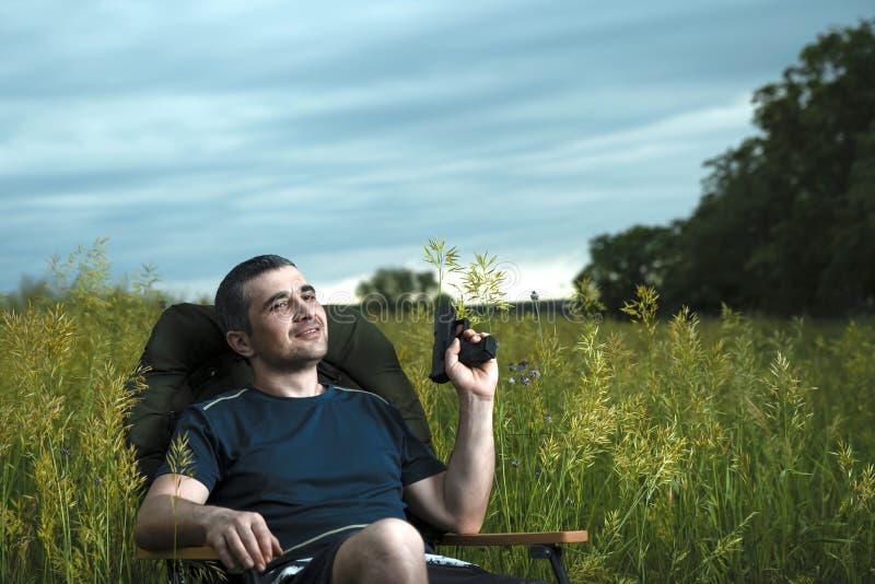 Konceptualny wizerunek dopatrywanie filmy w nowożytnych technologiach, młody człowiek siedzi w wygodnym krześle na naturze pod ot zdjęcia stock