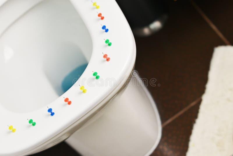 Konceptualny wizerunek hemoroid choroba z barwiącymi thumbtacks na toaletowego pucharu pokrywie obrazy royalty free
