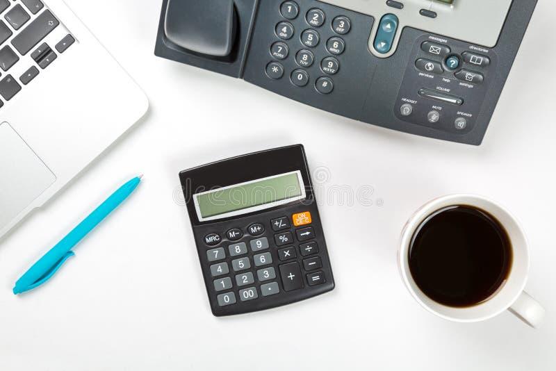 Konceptualny workspace lub biznesu pojęcie Laptop z filiżanką kawy, błękitnym pióro, nowożytny IP telefon i kalkulator na bielu,  zdjęcia royalty free