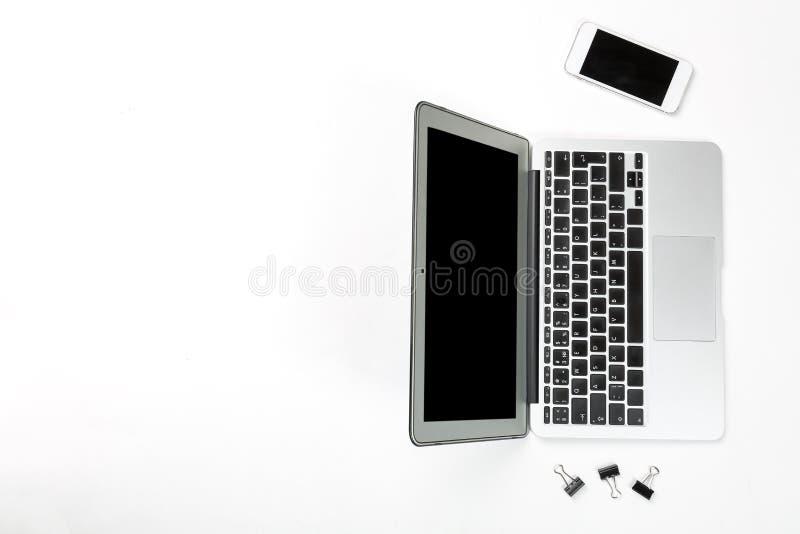 Konceptualny workspace lub biznesu pojęcie Laptop z mobilnym komórkowym telefonem i czarnymi papierowymi klamerkami na białym tle fotografia royalty free
