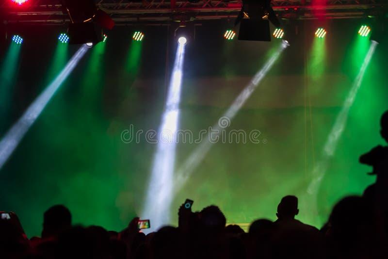 Koncertowy tłum uczęszcza koncert, ludzie zaświeca sylwetki są widoczne, backlit sceną Nastroszone ręki i mądrze telefony są visi obraz royalty free