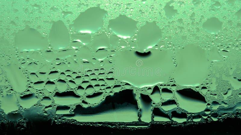 Kondensation, Dampf, Regen, Wasser-Tropfen von verschiedenen Größen auf einer Glasoberfläche Grüne Tone Color stockbild