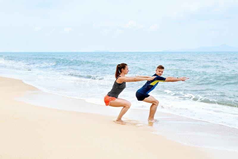 Konditionövningar Sunda par som Squatting och att öva på stranden royaltyfri foto