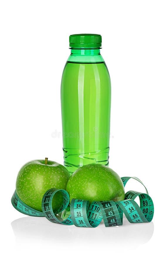 Kondition, begrepp för viktförlust med gröna äpplen, flaska av dricksvatten och måttband som isoleras på vit arkivfoto