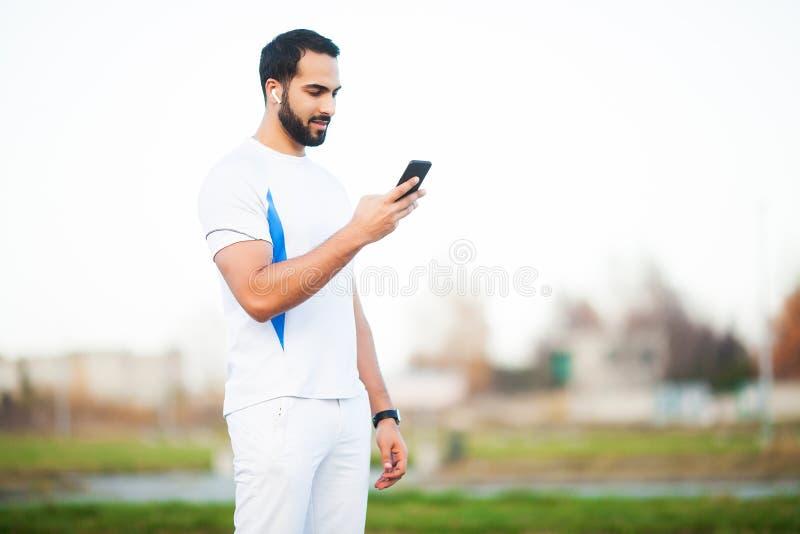 Kondition Den unga mannen som utarbetar i staden, parkerar och anv?nder hans mobiltelefon arkivfoton