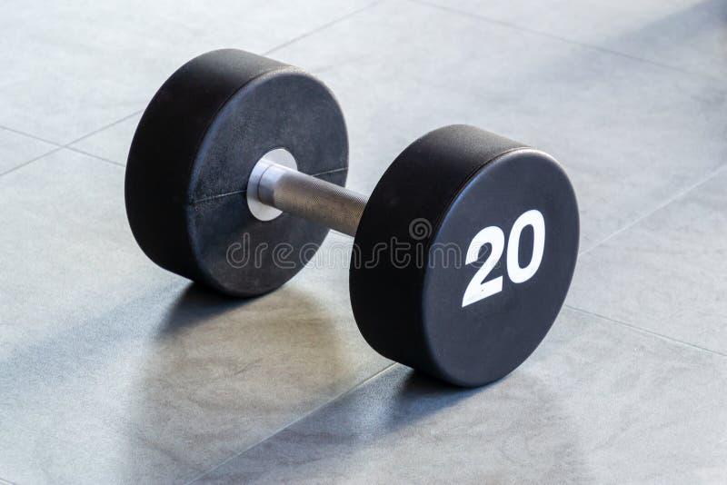 Kondition- eller bodybuildingbegreppsbakgrund Svart järnhantel på golvet i idrottshallen arkivfoto