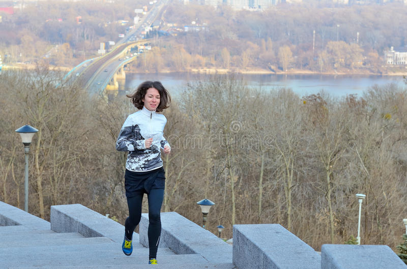 Kondition i staden, kvinnalöpare som joggar med den härliga sikten, spring och utarbetar i vinter royaltyfria bilder