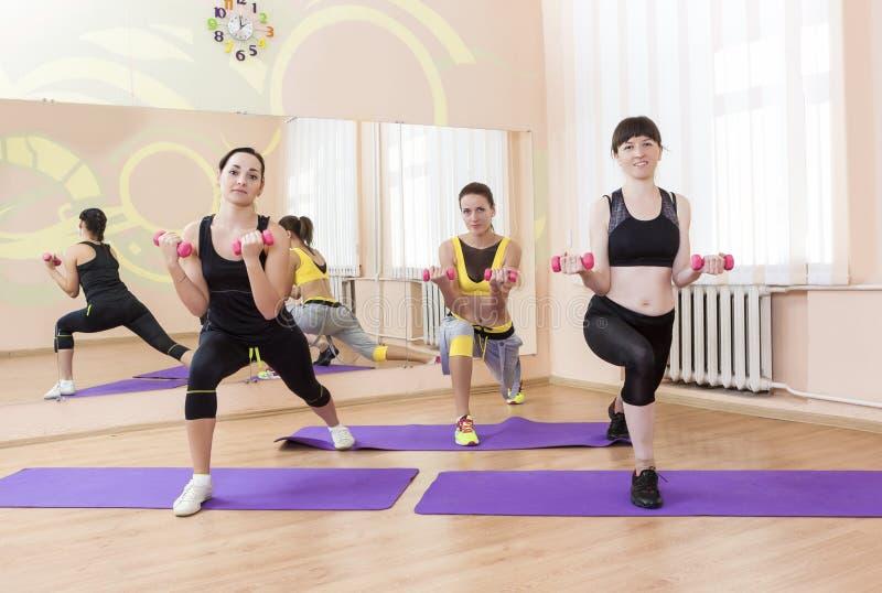 Kondition- och sportbegrepp Utföra för tre kvinnor för Caucasian färdigt arkivfoto