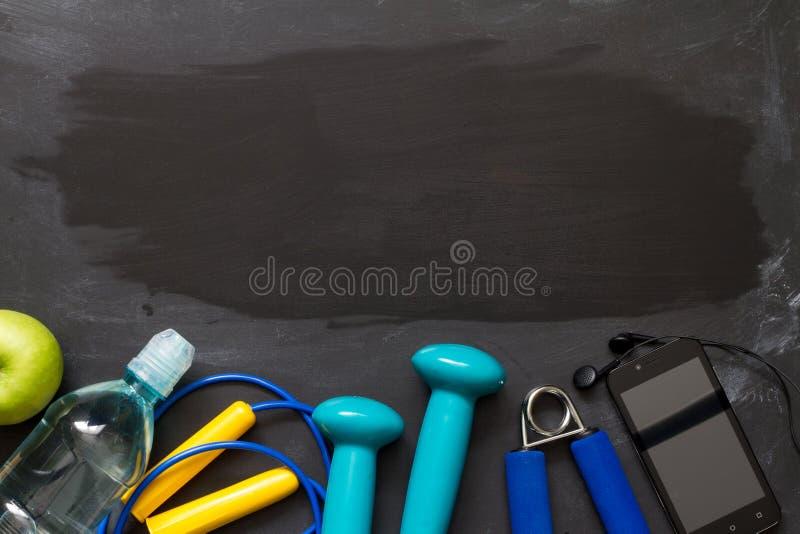 Kondition- och sportkugghjul på svart tavla royaltyfri fotografi