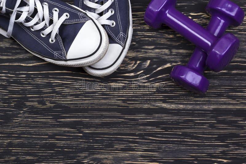 Kondition- och sportutrustning: gymnastikskor hantlar på träbakgrund arkivbild