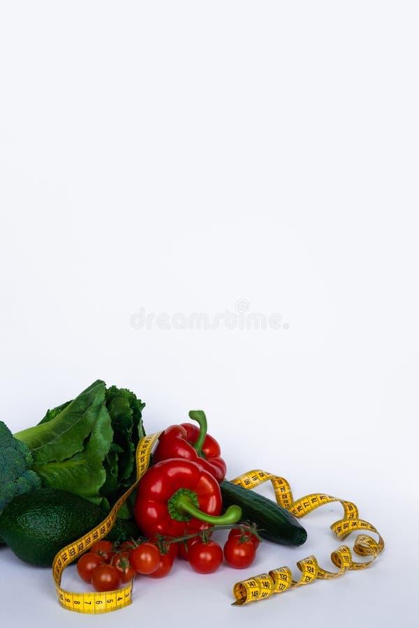 Kondition och sund mat bantar begrepp Nya gröna grönsaker som mäter bandet på vit bakgrund royaltyfri foto