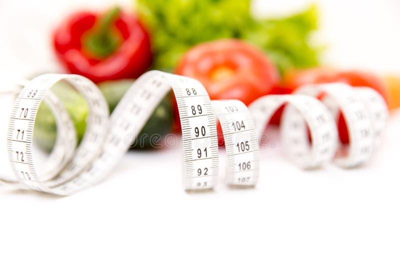 Kondition och sund mat bantar begrepp Nya gröna grönsaker som mäter bandet som isoleras på vit bakgrund closeup royaltyfri foto