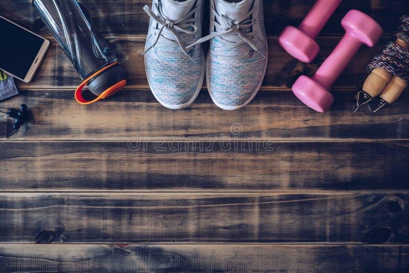Kondition och sunt aktivt livsstilbakgrundsbegrepp Utbildande gymnastikskor, hantlar, hopprep, vattenflaska, smart telefon och fotografering för bildbyråer