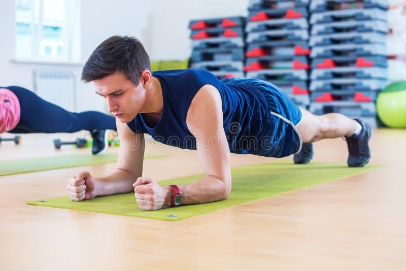 Kondition som utbildar den idrotts- sportiga mannen som gör plankaövning i idrottshall- eller yogagrupp som övar genomkörare arkivfoto