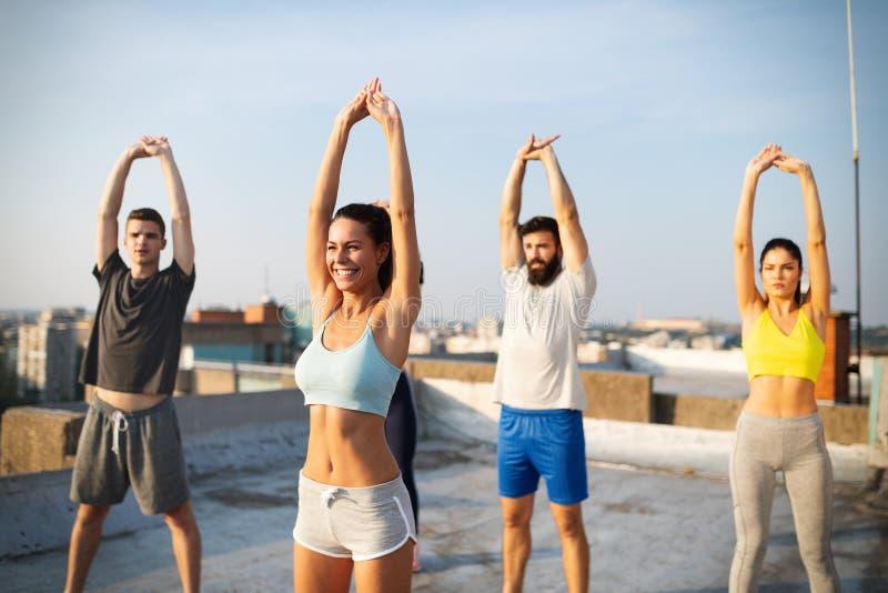 Kondition, sport, kamratskap och sunt livsstilbegrepp Grupp av lyckligt öva för folk royaltyfria bilder