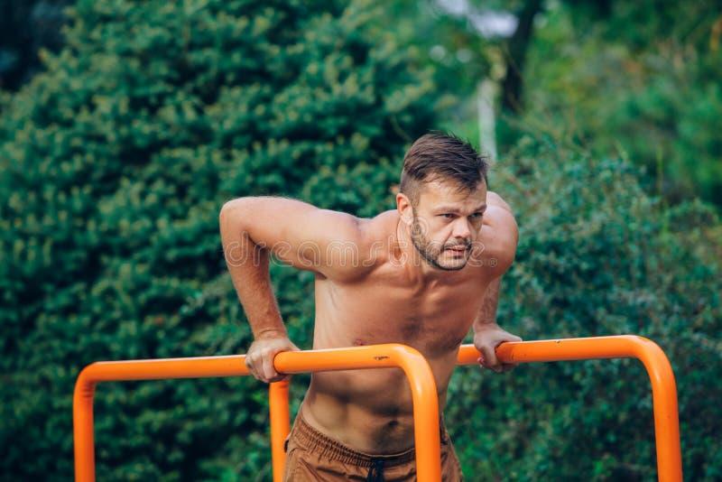 Kondition sport och att öva, utbildnings- och livsstilbegrepp - den unga mannen som gör triceps, doppar på barr utomhus royaltyfria foton