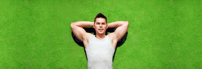 Kondition-, sport- och semesterbegrepp - idrottsman som kopplar av att ligga på ett gräs i sommardag, stilig man som vilar funder royaltyfria foton