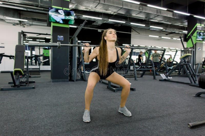 Kondition, sport, powerlifting och folkbegrepp - sportig nätt kvinna som övar med skivstången i idrottshall arkivfoto
