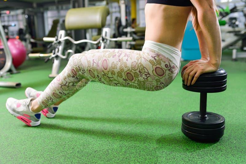 Kondition sport som övar livsstil - den färdiga kvinnan som gör triceps, doppar på idrottshallen Övningar med egen kroppsvikt royaltyfri bild