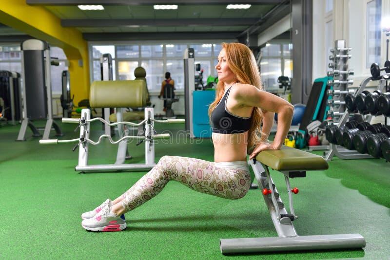 Kondition sport som övar livsstil - den färdiga kvinnan som gör triceps, doppar på idrottshallen Övningar med egen kroppsvikt royaltyfri foto