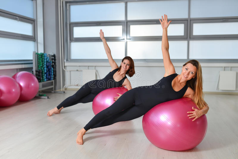 Kondition sport som övar livsstil - gruppen av kvinnor som gör övningar med passformen, klumpa ihop sig i en Pilates grupp på idr arkivfoton