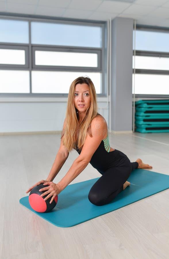 Kondition sport som övar livsstilen - färdig kvinna i bodysuiten som poserar på mattt med medicinbollen på idrottshallen royaltyfria foton