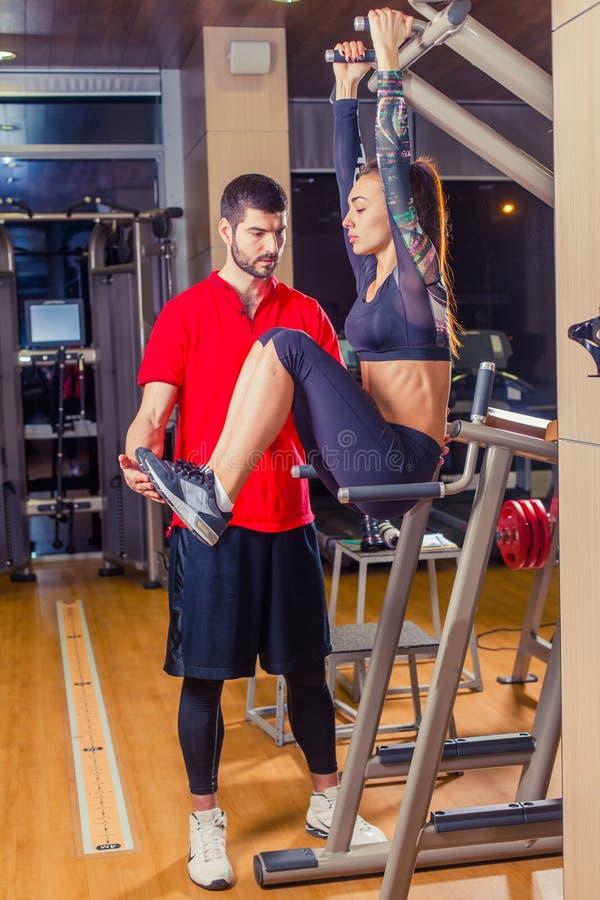 Kondition, sport, utbildning och folkbegrepp - den personliga instruktörportionkvinnan som arbetar med buk- muskler, trycker på p arkivfoto