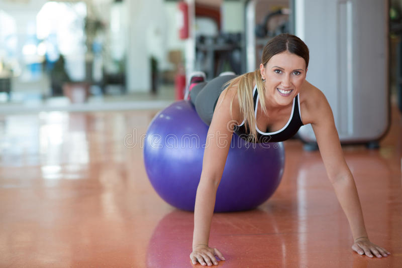 Kondition, sport, utbildning och folkbegrepp - le kvinnan som böjer buk- muskler med övningsbollen i idrottshall royaltyfri foto