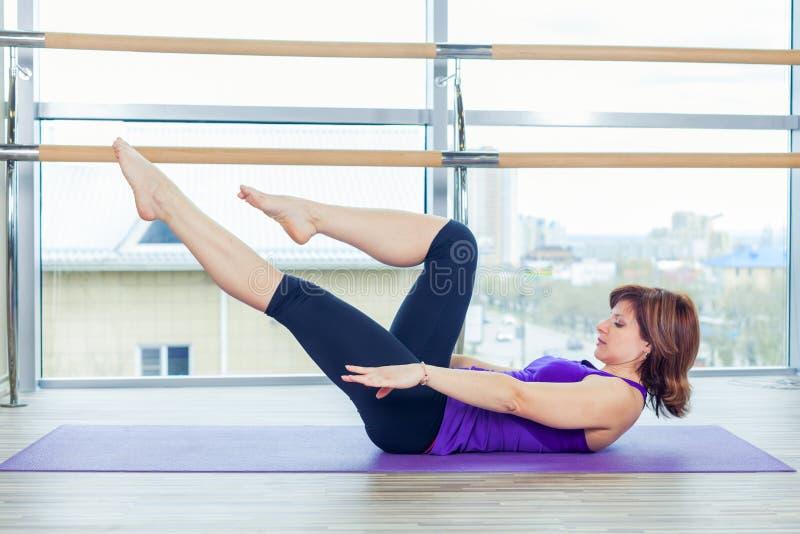 Kondition, sport, utbildning och folkbegrepp - le kvinnan som gör buk- övningar på mattt i idrottshall royaltyfri bild