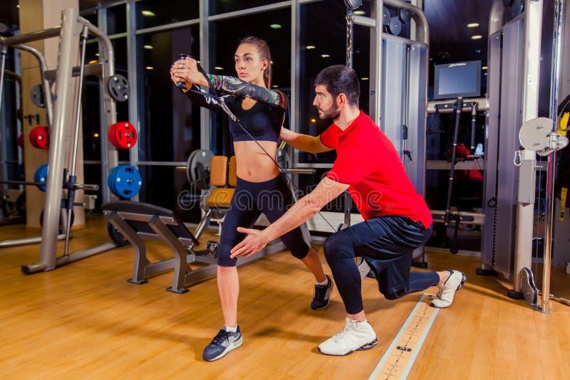 Kondition, sport, utbildning och folkbegrepp - personlig instruktörportionkvinna som arbetar med i idrottshall fotografering för bildbyråer