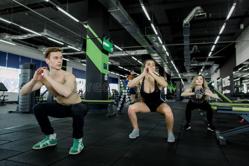 Kondition-, sport-, utbildnings-, idrottshall- och livsstilbegrepp - grupp av att le folk som övar i idrottshallen som gör squats royaltyfri bild
