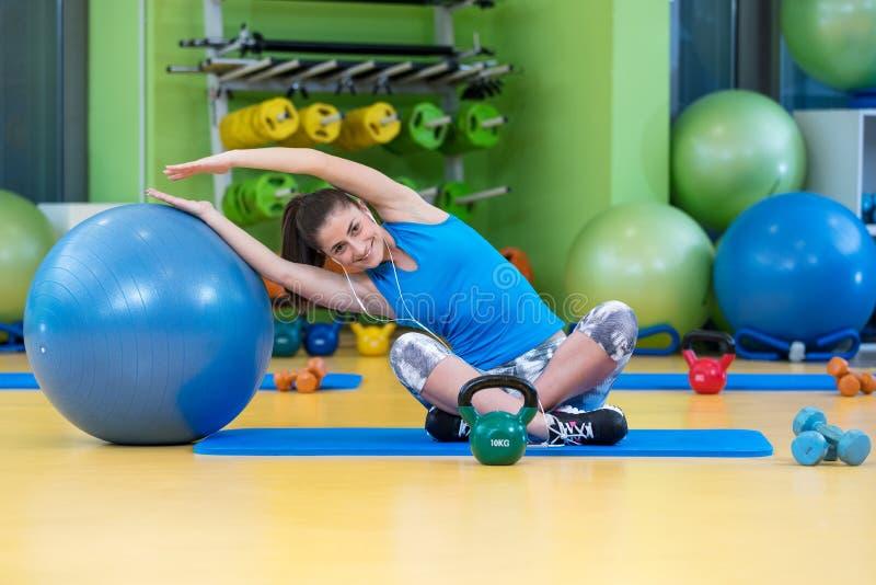Kondition-, sport-, utbildnings-, idrottshall- och livsstilbegrepp - ung kvinna som gör övning på konditionboll royaltyfria foton