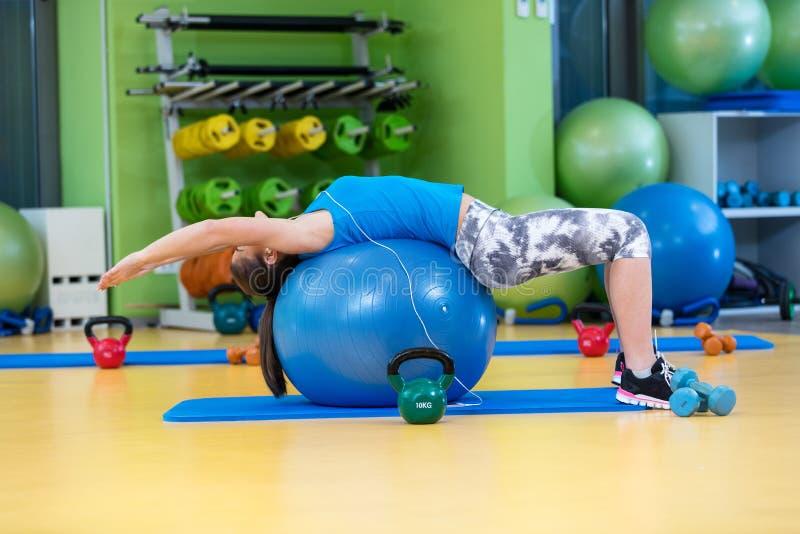 Kondition-, sport-, utbildnings-, idrottshall- och livsstilbegrepp - ung kvinna som gör övning på konditionboll arkivfoto