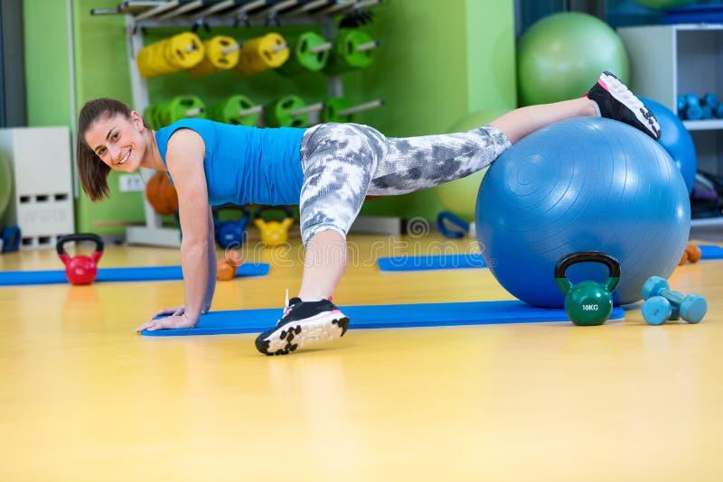 Kondition-, sport-, utbildnings-, idrottshall- och livsstilbegrepp - ung kvinna som gör övning på konditionboll arkivbild