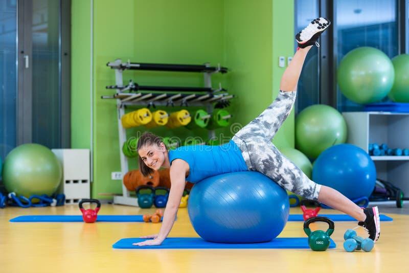 Kondition-, sport-, utbildnings-, idrottshall- och livsstilbegrepp - ung kvinna som gör övning på konditionboll royaltyfria bilder