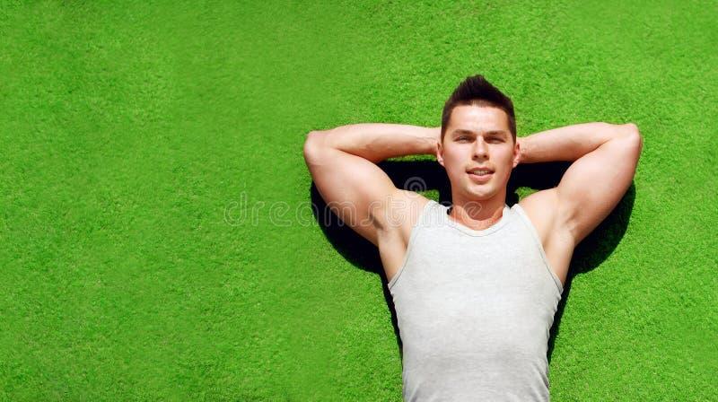 Kondition sportbegrepp - idrottsman som kopplar av att ligga på gräset arkivfoto