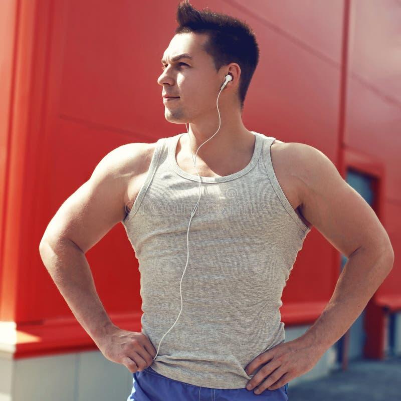Kondition sportbegrepp - ståendeidrottsmannen lyssnar till musik, når han har utbildat royaltyfria foton