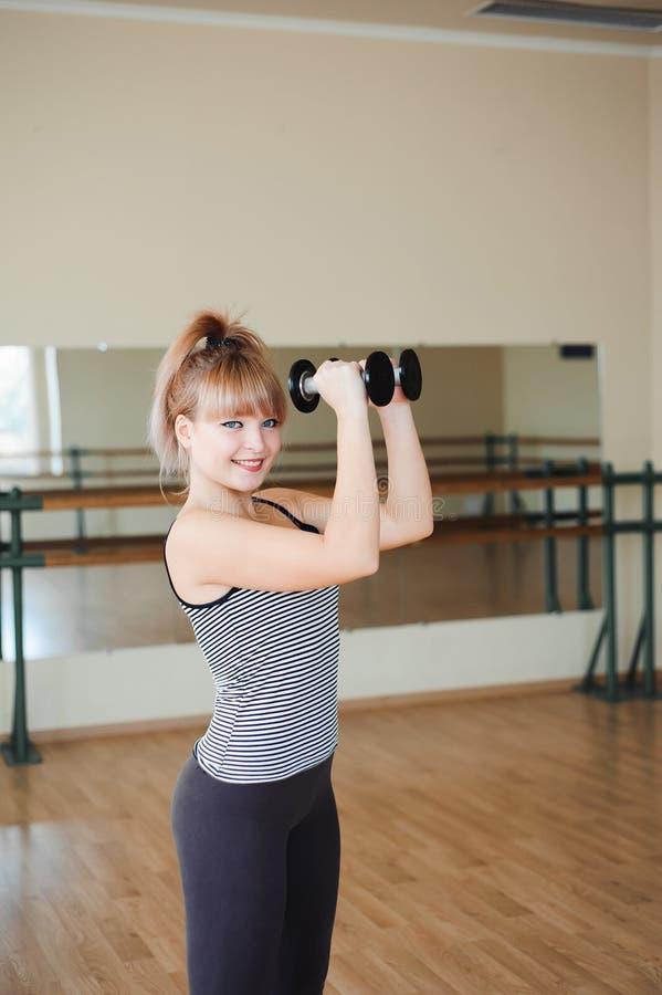 Kondition sportlivsstil - attraktiv ung kvinna som gör övningar för lyfta för vikt på idrottshallen arkivbild
