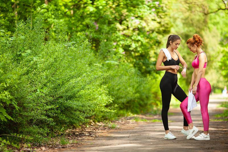 Kondition Två kvinnliga löpare som sträcker ben utomhus parkerar in, i sommar arkivfoton