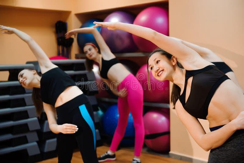 Kondition, utbildning, aerobics och folkbegrepp Härliga kvinnor som övar aerobics i konditionklubba arkivfoton