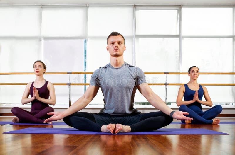 Kondition, yoga och sunt livsstilbegrepp - grupp människor som gör lotusblommaskyddsremsagest och mediterar, i placerat, poserar  royaltyfri fotografi