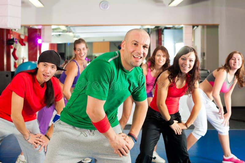 Kondition - Zumba dansgenomkörare i idrottshall arkivfoton