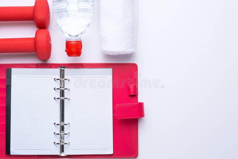 Konditionbakgrund med flaskan av vatten, hantlar och anteckningsboken ovanför sikt arkivfoto