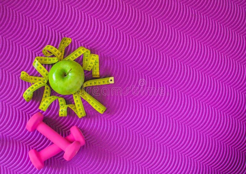 Konditionbakgrund med hantlar och att mäta bandet och äpplet Sunt livsstilbegrepp med kopieringsutrymme royaltyfri foto